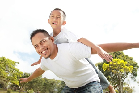 piggyback ride: Portrait of father giving his son piggyback ride against sky