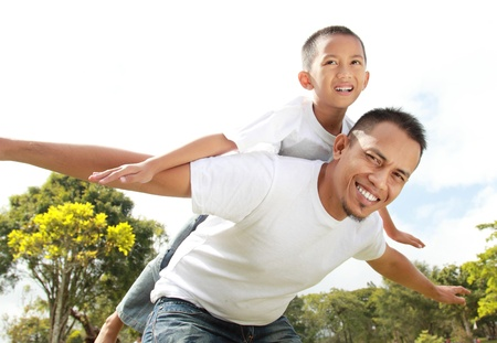father and son: Man smiling giving young boy piggyback ride
