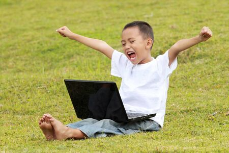 happy young little boy celebrating success playing laptop on the grass photo