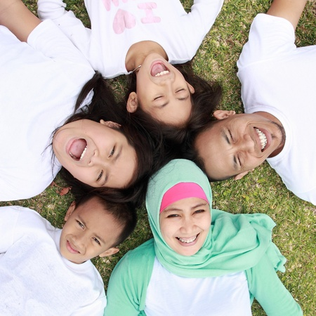 femme musulmane: Bonne grande famille souriante et couché sur l'herbe