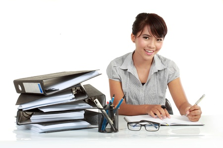 Portrait of an adorable business woman working at her desk with paperwork photo