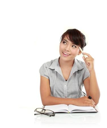 donna pensiero: Giovane donna d'affari pensare con una penna in mano al suo posto di lavoro
