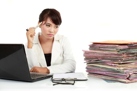 stressed business woman: young business woman with laptop and many paper stressed at work Stock Photo