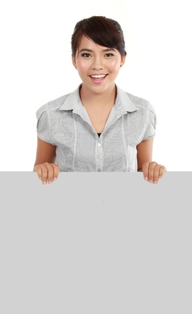 smiling young business woman showing blank signboard, isolated on white background photo