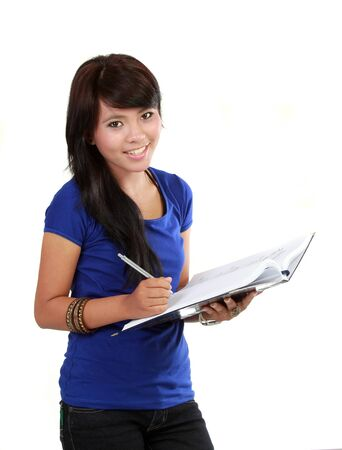 a young women writing in a notebook isolated on a white background. photo