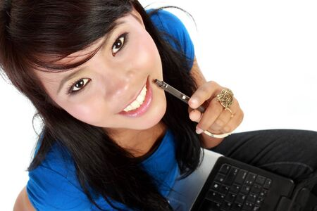 Top view of asian young lady looking up while lying on floor with a laptop photo