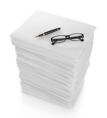 close up of pen and glasses in a stack of papers on white background photo