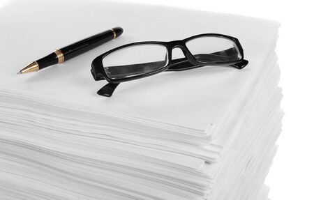 close up glasses and pen on a stack of paper. in isolated white background photo