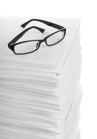Stack of paper and glasses lying on it with white background photo