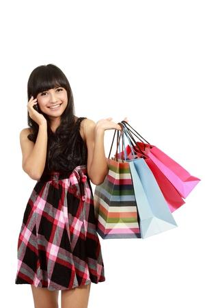 compras compulsivas: mujer joven de compras y llamar a sus amigos en el fondo aislado