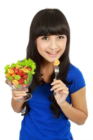 Pretty girl eating fruit salad, healthy fresh breakfast, dieting and health care concept. in white background Stock Photo - 11093138