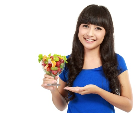 Closeup portrait of an attractive young woman eating fruit salad in isolated background Stock Photo - 11093113