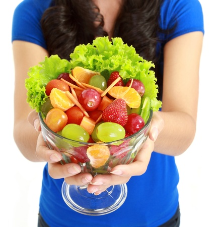Closeup of a pretty young lady eating fruit salad in white background photo