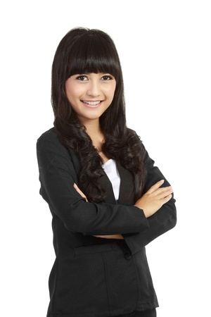 Portrait of a happy young business woman standing with folded hand against white background photo