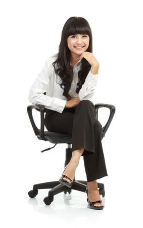 Portrait of beautiful young woman sitting on chair isolated over white background photo
