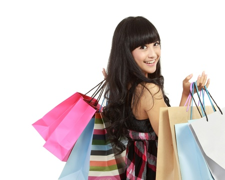 Shopping woman happy smiling holding shopping bags isolated on white background. Lovely fresh young Asian female model. Stock Photo - 11093048