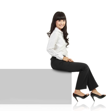 Woman smiling sitting on horizontal banner edge. Happy businesswoman showing sign with lot of copy space. Isolated on white background in full body. Stock Photo - 11092962