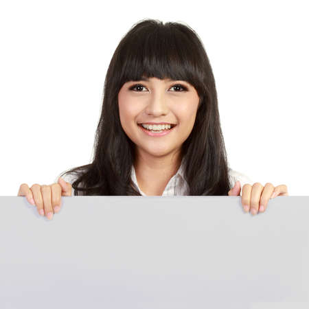 Happy smiling young business woman showing blank signboard, over white background photo
