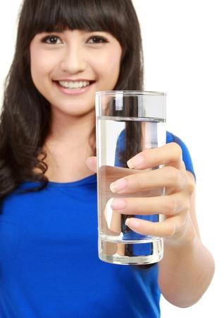 tomando refresco: mujer joven y sana con un vaso de agua fresca en el fondo blanco