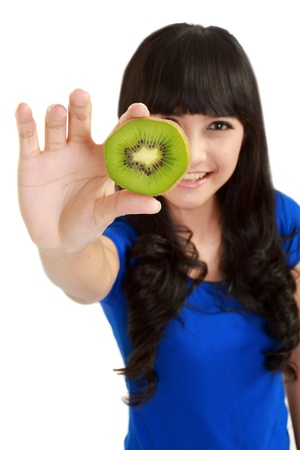 Pretty young woman holds kiwi in front of her eyes. in isolated white background photo