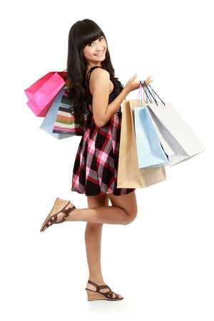 Shopping woman happy smiling holding shopping bags isolated on white background. Lovely fresh young Asian female model. photo