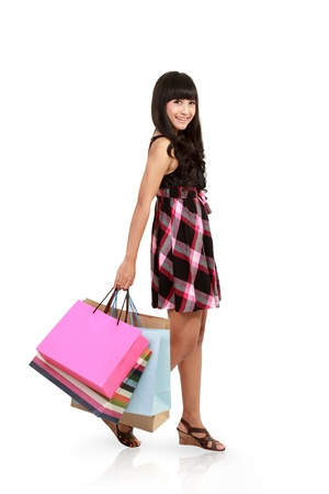side light: Side view of woman holding shopping bags against white background