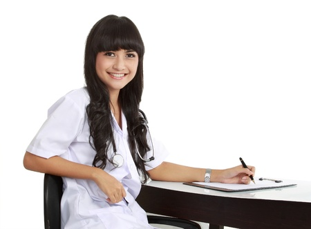 Young woman doctor writing prescription at desk isolated on white photo