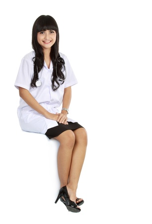 A female doctor sitting in a blank space isolated over white photo