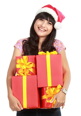 Christmas woman holding gifts wearing Santa hat. Standing in full body isolated on white background. Smiling woman portrait of a beautiful Asian model. photo