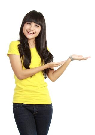 Retrato de mujer joven y sonriente que muestra un producto imaginario en el fondo blanco