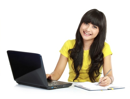 Cheerful girl with laptop and write on a books, isolated white background