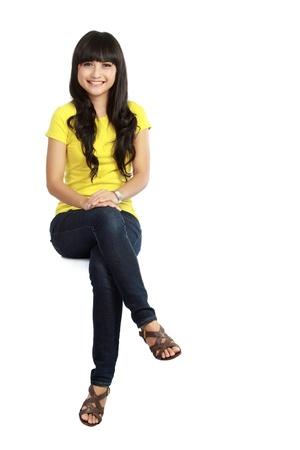 donna seduta sedia: Bella ragazza seduta informale sul grande vuoto segno manifesto cartellone con sacco di spazio copia. Sorridente asian model giovane donna. Isolato su sfondo bianco Archivio Fotografico