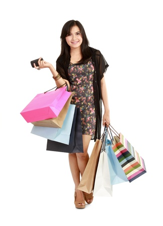 Lucky shopping girl with the phone. Isolated on white background photo