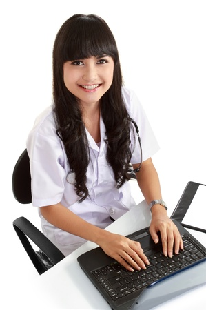 Beautiful female doctor working with her laptop while sitting in her office. in isolated background photo