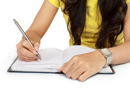 Close-up of a girl writing in a notebook isolated over white background Stock Photo - 11318467