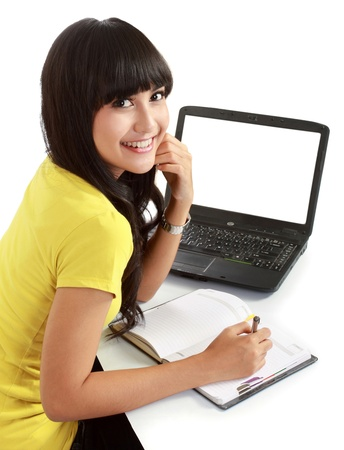 Happy female student with a laptop and notebooks . isolated over white photo