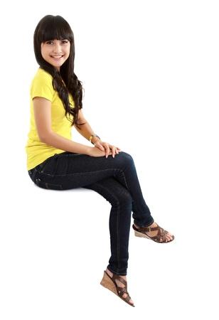 persona sentada: Chica linda sentada casual en gran cartel en blanco del cartel cartel con gran cantidad de espacio de la copia. Sonriente mujer joven modelo asi�tico. Aislado sobre fondo blanco