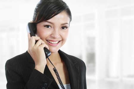 phone conversation: Portrait of charming young business woman on phone call at office Stock Photo