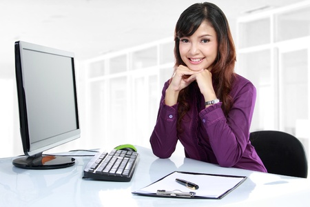office environment: Portrait of a beautiful business woman working on her desk in an office environment. Stock Photo