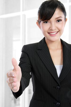 Beautiful business woman offering handshake on her office photo