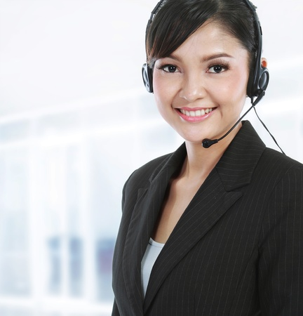 Young beautiful customer service operator with headset on her office Stock Photo