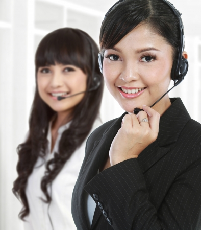 customer services: Portrait of a successful female call centre employee wearing a headset. in white background