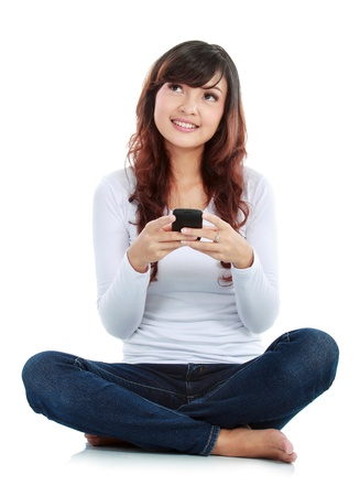 Woman sitting on floor and text messaging on a mobile phone while thinking what to say. isolated over white background photo