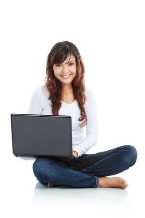 asian laptop: Young female sitting cross-legged on floor with laptop isolated white background