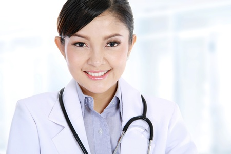 Smiling medical doctor with stethoscope. In her office photo