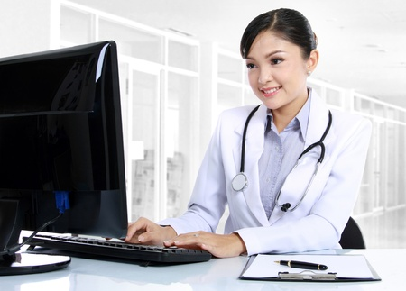 nurse computer: front view of smiling woman doctor working on computer Stock Photo