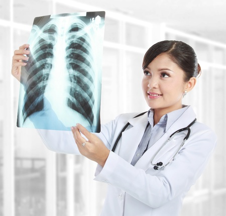 healthcare office: Female doctor looking at an x-ray in her office