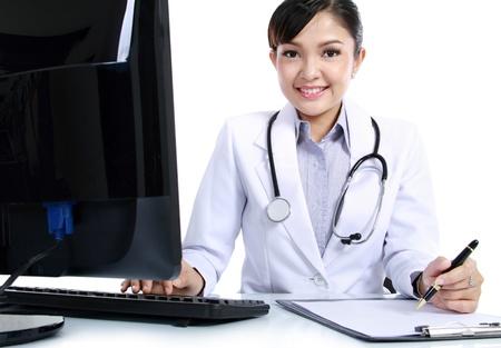 buena salud: mujer médico que trabaja en su oficina con un ordenador y tablero de clip en el fondo aislado