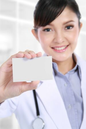 Smiling medical doctor woman holding and showing blank business card photo