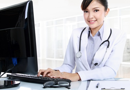 computer model: smiling doctor woman sitting on her office with computer set and clip board on her table